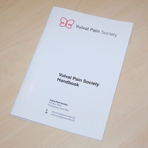 Image shows a photo of the Vulval Pain Society Handbook, which is A4-sized with a soft white cover.